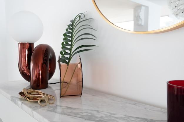 Composição elegante do candeeiro de mesa espelho vermelho com ouro estacionário em cima de mármore branco, com espaço de cópia na parede branca
