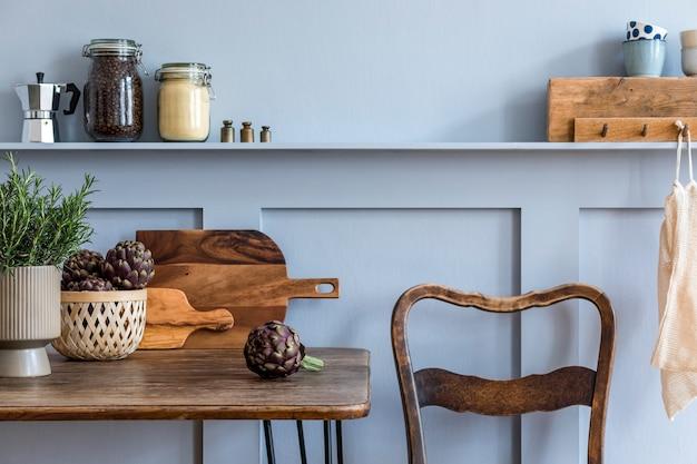 Composição elegante do interior da cozinha com mesa familiar de madeira, cadeiras, vegetais, ervas, plantas, frutas, suprimentos alimentares e acessórios de cozinha no conceito cinza de decoração para casa.