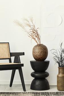 Composição elegante do interior da sala de estar branca com cadeira de design, banquinho de madeira preto, flores secas em um vaso, decoração em carpete e pinturas de arte na parede.
