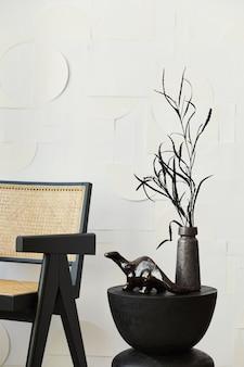 Composição elegante do interior da sala de estar branca com cadeira de design, banquinho de madeira preto, flores secas em um vaso e pinturas artísticas na parede.