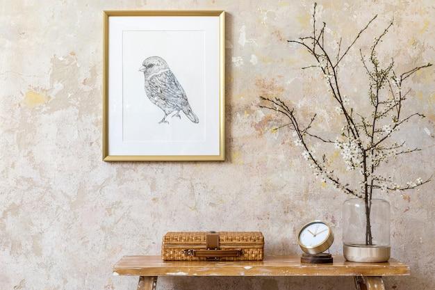 Composição elegante do interior da sala de estar com moldura dourada, banco de madeira, decoração, flores secas em um vaso, relógio, mala e acessórios pessoais elegantes na decoração moderna da casa.