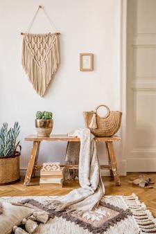 Composição elegante do interior da sala de estar com moldura simulada, banco de madeira, travesseiro, xadrez, bolsa de mulher, livros, cactos, macramê, planta, decortaion e acessórios pessoais elegantes na decoração moderna.