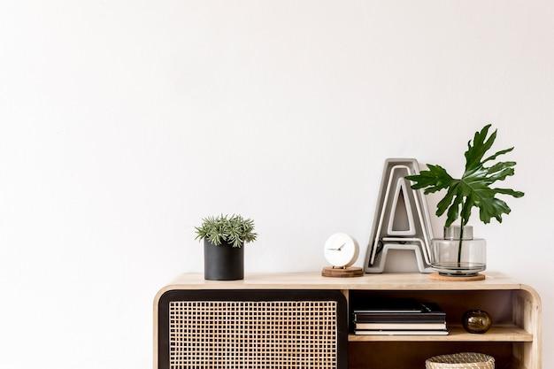 Composição elegante do interior da sala de estar com parede branca, folhas verdes em um vaso de vidro na cômoda escandinava de madeira. conceito minimalista. copie o espaço.