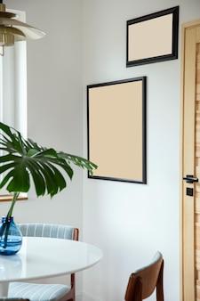 Composição elegante do interior da sala de jantar com mesa de design, cadeiras, folha tropical em um vaso, pôster e decoração elegante na decoração da casa. modelo.