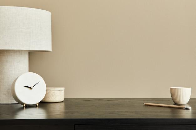 Composição elegante do interior do escritório com mesa preta, lâmpada projetável, relógio branco, xícara de café e caneta