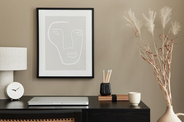 Composição elegante do interior do escritório em casa com mesa de madeira preta, cadeira, flores secas em um vaso, laptop, moldura, abajur de mesa de design, relógio e acessórios de escritório elegantes.