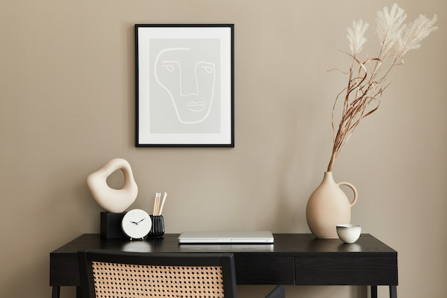Composição elegante do interior do escritório em casa com mesa de madeira preta, cadeira, flores secas em um vaso, laptop, moldura, xícara de café, relógio e acessórios de escritório elegantes.