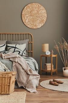 Composição elegante do interior do quarto com cama de madeira, móveis, carpete, banqueta, decoração de vime, vasos e acessórios elegantes.