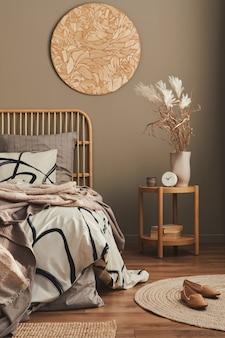 Composição elegante do interior do quarto com cama de madeira, móveis, decoração em carpete, banquinho, decoração de vime, vasos e acessórios elegantes.