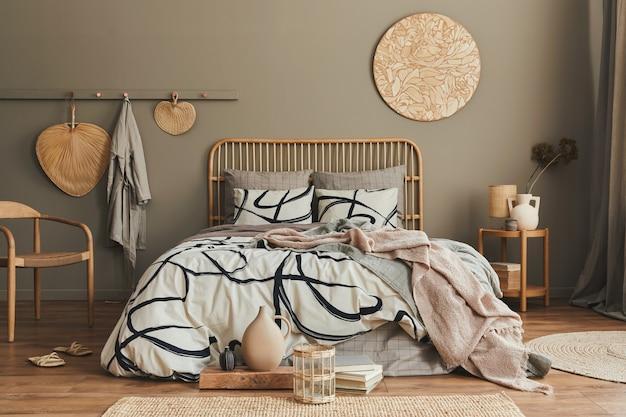 Composição elegante do interior do quarto com cama de madeira, móveis, flores secas em um vaso, decoração de vime e acessórios elegantes.