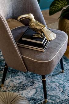 Composição elegante e luxuosa de poltrona cinza de design com livros, escultura, planta em pote de ouro e acessórios elegantes. design de interiores. encenação em casa moderna. fechar-se.
