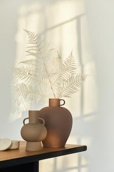 Composição elegante na mesa de madeira com vasos de design com flores secas. lindas sombras na parede. conceito abstrato no interior moderno.