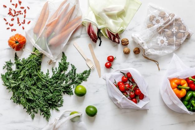 Composição elegante na mesa de mármore com zero sacos de resíduos, nozes, sementes, ovos, vegetais biológicos e frutas ecológicas. cuidando da terra. pare de plástico.