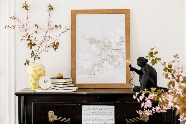 Composição elegante no interior da sala de estar com piano preto, mapa de pôster, flores secas, relógio branco, livro, lâmpada e acessórios pessoais elegantes em decoração moderna.