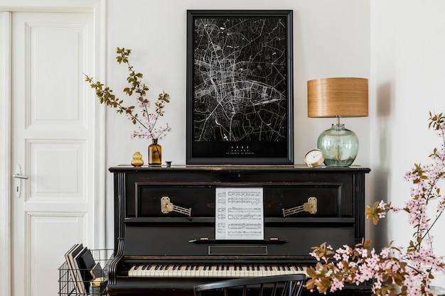 Composição elegante no interior da sala de estar com piano preto, mapa de pôster, flores secas, relógio de ouro, lâmpada de design e acessórios pessoais elegantes em decoração moderna.