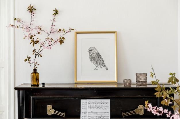Composição elegante no interior da sala de estar com piano preto, moldura dourada, flores secas e acessórios presonais elegantes na decoração moderna.