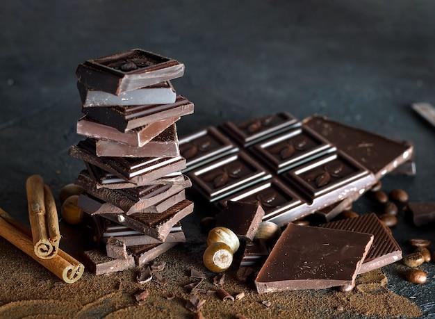 Composição em barras e pedaços de diferentes leite e chocolate amargo, cacau ralado em um fundo marrom.