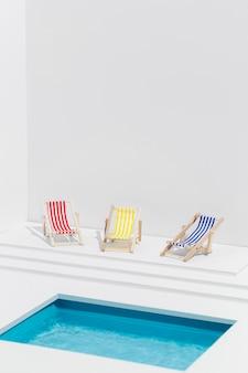 Composição em miniatura de espreguiçadeiras ao lado da piscina