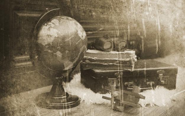 Composição em um globo vintage de piso de madeira com uma velha mala de couro com objetos para viagens
