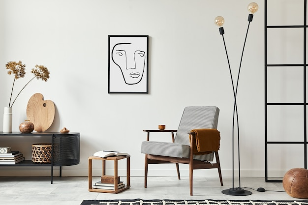 Composição escandinava elegante de sala de estar com poltrona de design, moldura preta, cômoda, banquinho de madeira, abajur, decoração, parede de loft e acessórios pessoais na decoração moderna da casa.