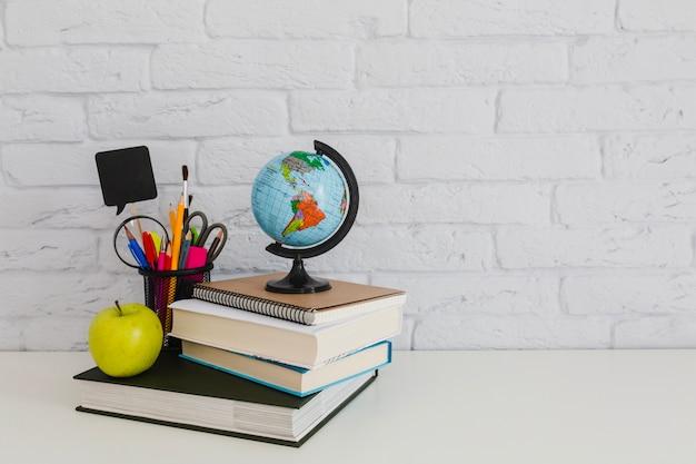 Composição escolar com livros, maçã e globo mundial