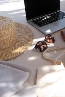 Composição estética criativa com acessórios de moda feminina. óculos de sol femininos elegantes, chapéu de palha, bolsa de compras, laptop no sofá branco com almofadas