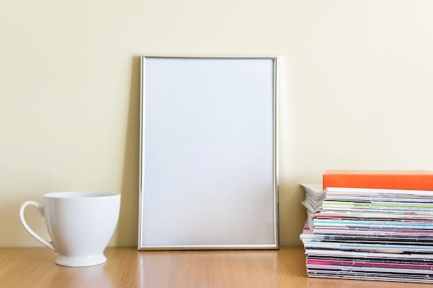 Composição estilo escritório com grande moldura em branco a4 prateado, copo de porcelana branca e pilha de revistas na superfície de madeira.