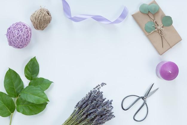 Composição festiva com flores, caderno, presentes, tesoura, fitas, folhas em um fundo branco, vista superior e moldura plana, floral