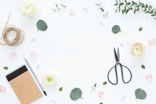 Composição festiva com flores, caderno, presentes, tesoura, fitas, folhas em um fundo branco, vista superior e plana leigos, quadro floral