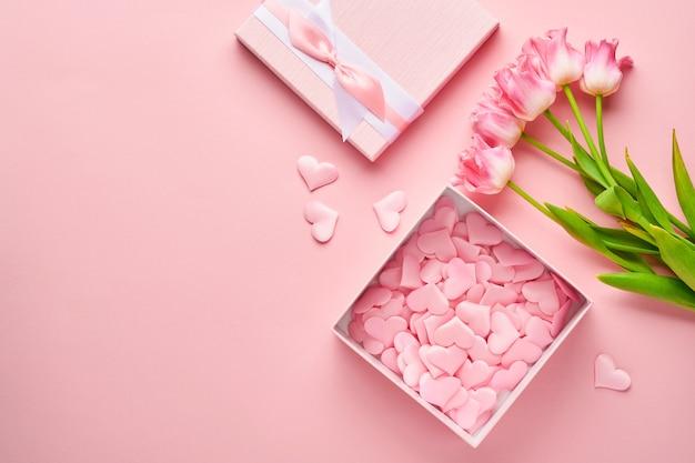 Composição festiva com lindas flores delicadas de tulipas em caixa redonda rosa sobre fundo claro.