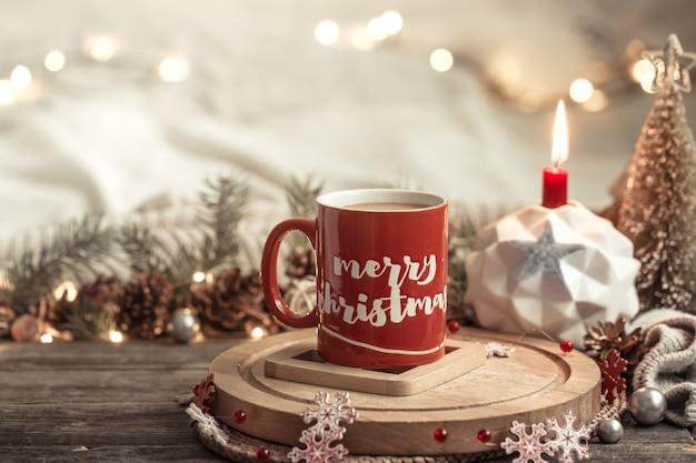 Composição festiva com um copo vermelho com a inscrição de feliz natal.