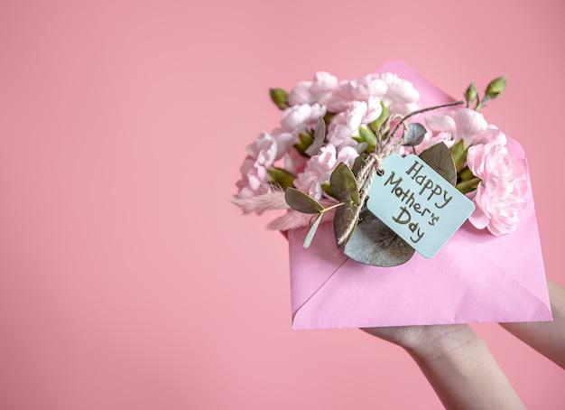 Composição festiva com um envelope com flores frescas e a inscrição feliz dia das mães plana leigos.