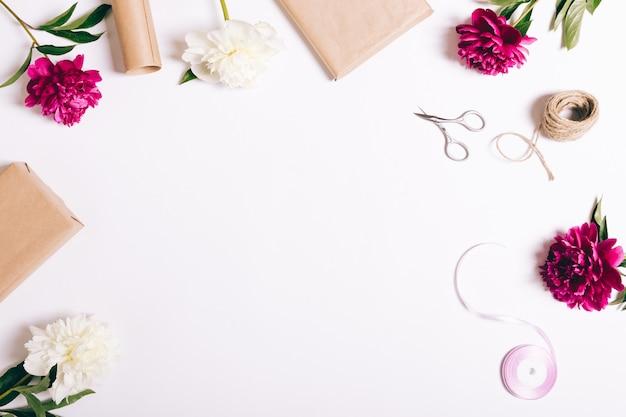 Composição festiva de flores e presentes na mesa branca