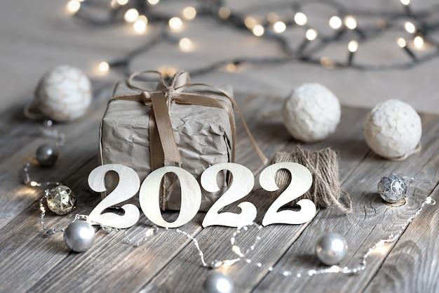 Composição festiva de natal com números de madeira 2022, caixa de presente e bolas de natal em fundo desfocado com bokeh.