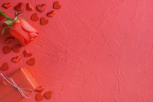 Composição festiva de rosa vermelha, caixa de presente amarrada e corações espalhadas em rosa para dia dos namorados