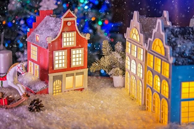 Composição festiva de um candeeiro em forma de uma velha casa europeia, um cavalo de brincar, ramos de abeto e cones