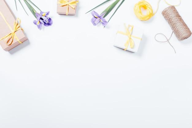 Composição festiva em fundo branco: flores, caixas com presentes, fitas