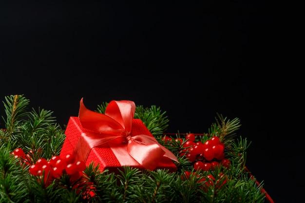 Composição festiva escura com caixa de presente presente vermelha de natal com laço de cetim, agulhas e frutas vermelhas.