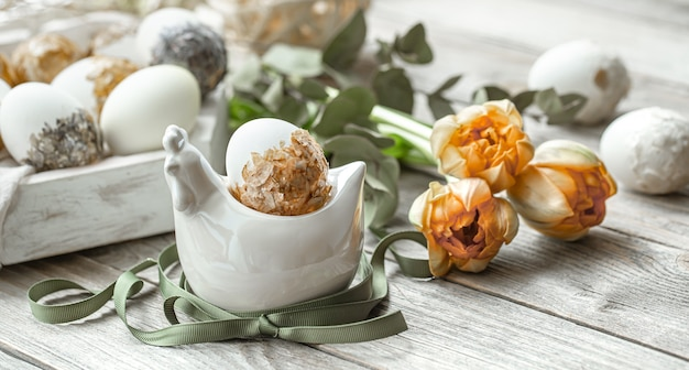 Composição festiva para o feriado da páscoa com ovos decorativos e flores frescas.
