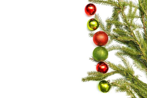Composição flatlay de natal com moldura vazia de bolas verdes vermelhas coloridas e galhos de árvores de abeto. decorações de ano novo em fundo branco. espaço da cópia do modelo do cartão de cumprimentos de maquete, horizontalmente, vista superior