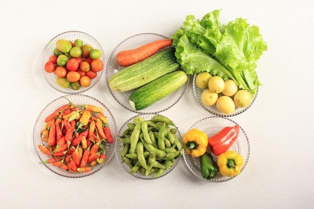 Composição flatlay de vegetais frescos na placa clara acima da mesa de creme. vibrance color pleasing eye. conceito de fazer dieta