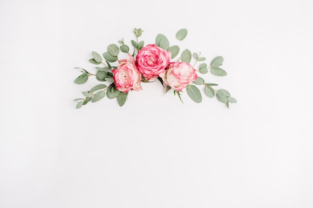 Composição floral com botões de flores de rosa rosa e eucalipto. camada plana, vista superior