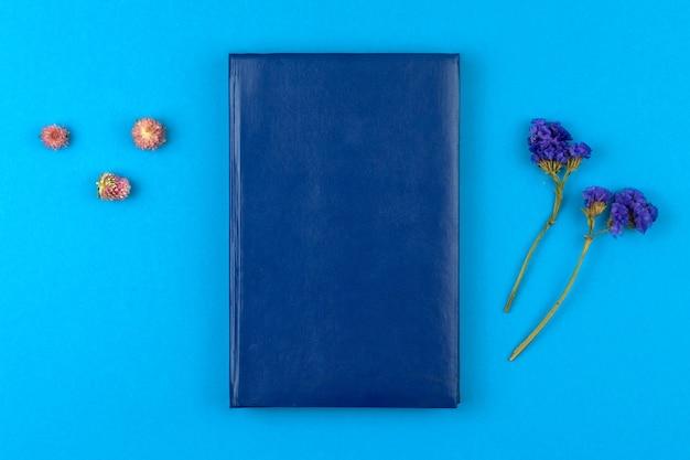 Composição floral com caderno de couro com espaço de cópia, fundo azul da área de trabalho do escritório, foto da vista superior