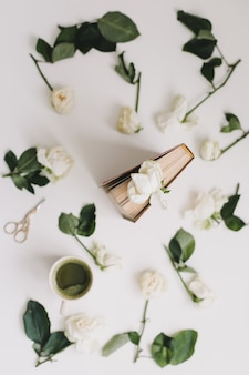 Composição floral com um livro com rosas brancas e uma xícara de chá verde matcha branco