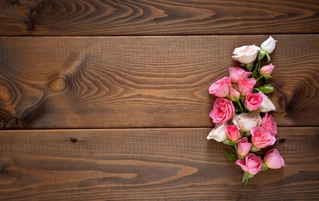 Composição floral com uma coroa de rosas cor de rosa em fundo de madeira. plano de fundo dia dos namorados.