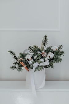 Composição floral de natal em uma caixa de chapéu branco com galhos de pinheiro, algodão, paus de canela e bolas de natal. o conceito de um ano novo e natal elegantes