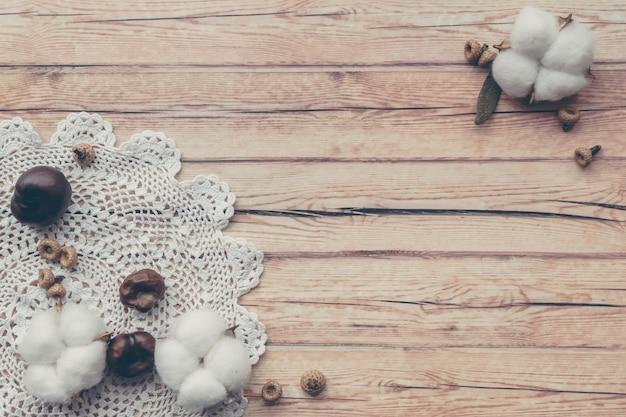 Composição floral de outono. flor macia branca secada do algodão e guardanapo feito malha na tabela de madeira.