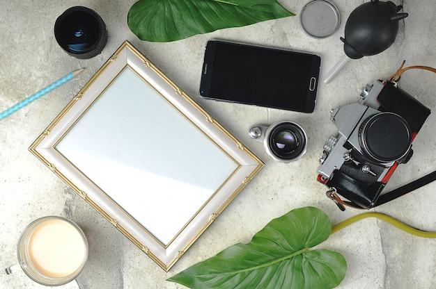 Composição fotográfica - uma câmera de filme antigo, lentes, uma moldura vazia e uma xícara de café