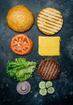 Composição home feita do hamburguer (receita). produtos para o hambúrguer clássico sobre um fundo escuro.