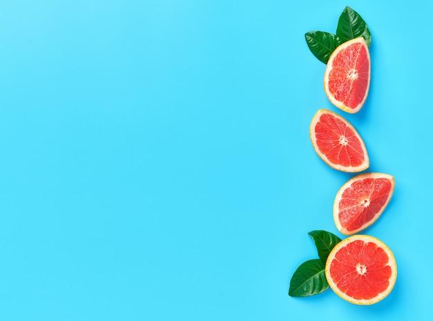 Composição linear de fatias de laranja madura com folhas verdes